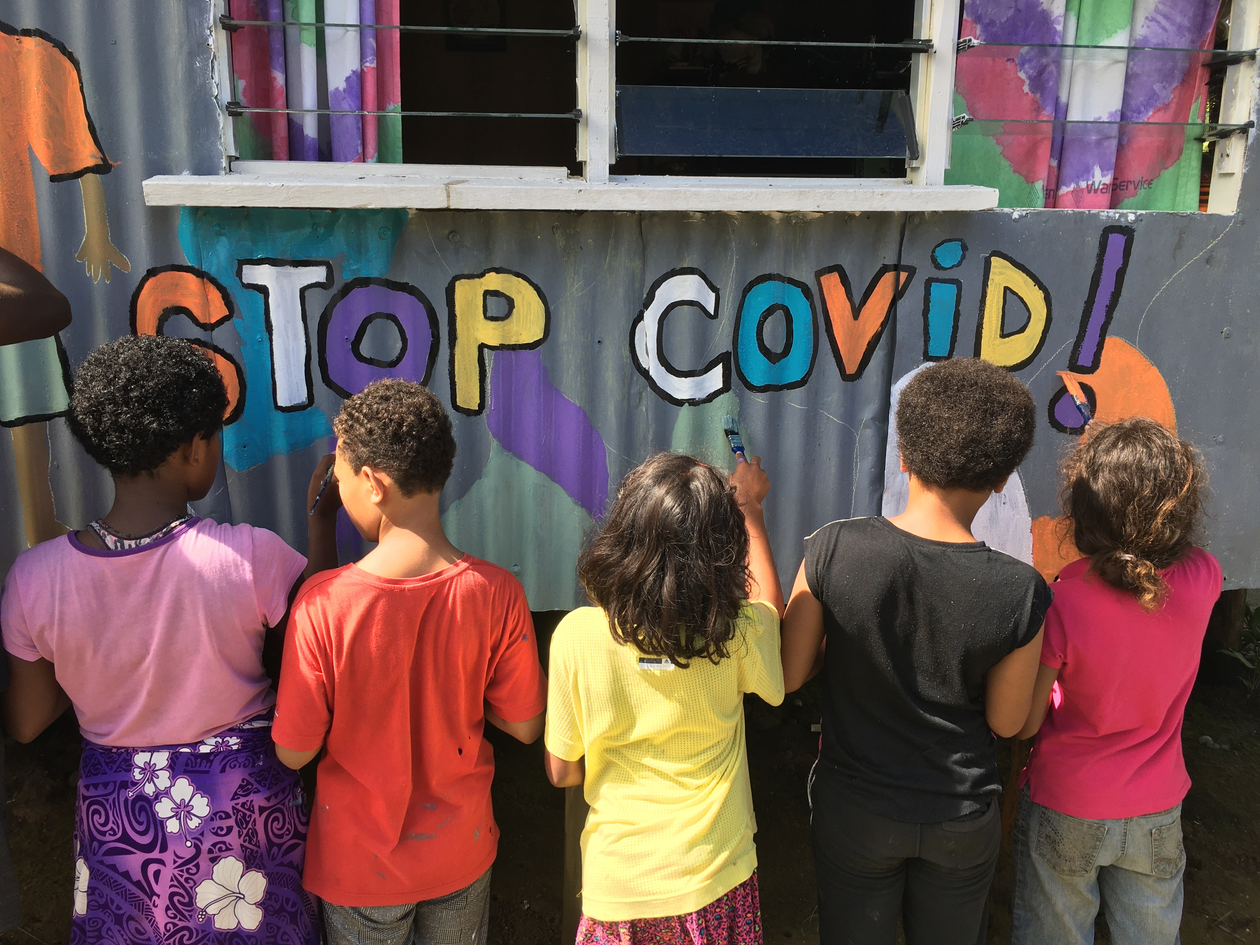 Youth painting a COVID-19 awareness mural in Vuniivi settlement Lami, Fiji