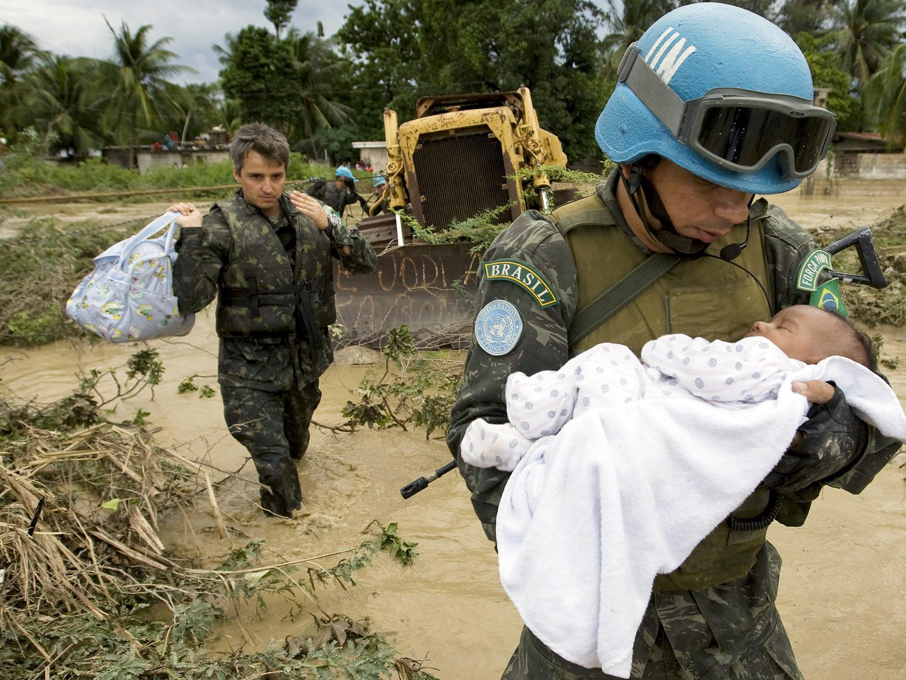UN peacekeeper carrying a infant whose family was impacted by flooding in Haiti in 2007