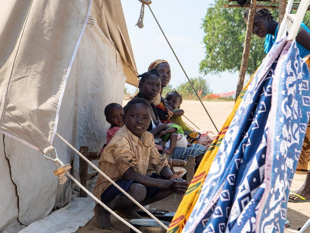 A family outside of their tent in the Taratara Camp, in Cabo Delgado province