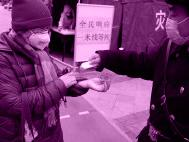A man giving hand sanitiser to another man in a street in China