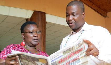 "At the UNISDR media training in Arusha Tanzania today, Rachel Nakitare, Chief Producer - TV, Kenya Broadcasting Corporation, reviews the flood coverage in Mozambique's leading newsweekly ""Domingo"" with the newspaper's editor, Maputo-based Jorge Ernesto Rungo."