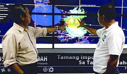 Alexander Pama (left), Executive Director of the Philippines' National Disaster Risk Reduction and Management Council, receives a briefing from a local meteorologist on the expected movement of Typhoon Hagupit. (Photo: Kenly Monteagudo)