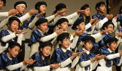 The song 'Bring Happiness to the World' has become a rallying call for the city of Kobe. Here children of Nishinada Elementary School perform it at JICA symposium on 18 Jan together with Mr. Usui who made this song two weeks after the earthquake. (Photo: UNISDR)