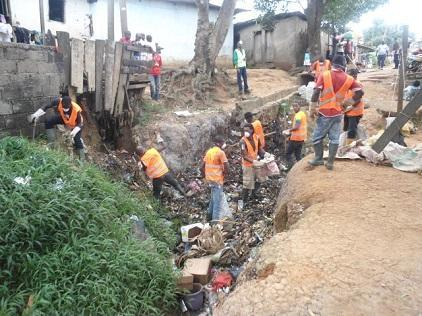 Local residents clear a trash-strewn drainage ditch in Nkolbikok, in Cameroon's capital Yaoundé, where the community has mobilized to reduce flood risk (Photo: Mairie de Yaoundé 6)
