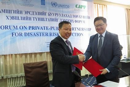 The Deputy Chief of the National Emergency Management Agency, Colonel Gombojav Ariunbuyan (left), and the President of the Mongolian National Chamber of Commerce and Industry, Mr Baatarjav Lkhagvajav, exchange copies of the agreement between the two sides. (Photo: UNISDR)