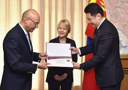 Mr. Sanjaya Bhatia (left), Head of UNISDR ONEA-GETI, receives the signing certificate of Ulaanbaatar, Darkhan and Erdenet cities  from Mr. Ukhnaa Khurelsukh, Deputy Prime Minister of Mongolia, in the presence of Ms. Beate Trankmann, UN Resident Coordinator and UNDP Resident Representative in Mongolia.