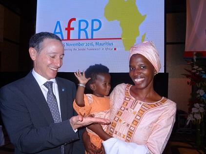 UNISDR head, Mr. Robert Glasser waits for a high-five from baby Chilal in the arms of her mother, Ms. Oumie Sissokho, Director of Operations, Gambia National Disaster Management Agency