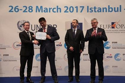 Robert Glasser, Special Representative of the UN Secretary-General for Disaster Risk Reduction (left) presents the Damir Cemerin Award to Erkan Samiloglu of Turkey's Ministry of Youth and Sports, watched by Mahmut Baş of fellow laureate the Directorate of Earthquake and Ground Research, Istanbul Metropolitan Municipality (centre right), and Turkish Deputy Prime Minister Veysi Kaynak (Photo: AFAD)