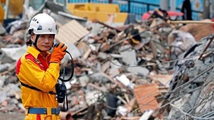 A rescuer speaks on the radio as he searches for survivors at collapsed building after an earthquake hit Hualien in Taiwan, February 8, 2018.