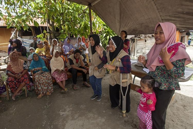 (c)Dwi Oblo/ASB Indonesia and the Philippines. Two members of a Disabled People's Organisation (DPO), wearing khaki vests, are delivering a hygiene promotion session for community members of Mantikole Village, Sigi, Central Sulawesi, Indonesia